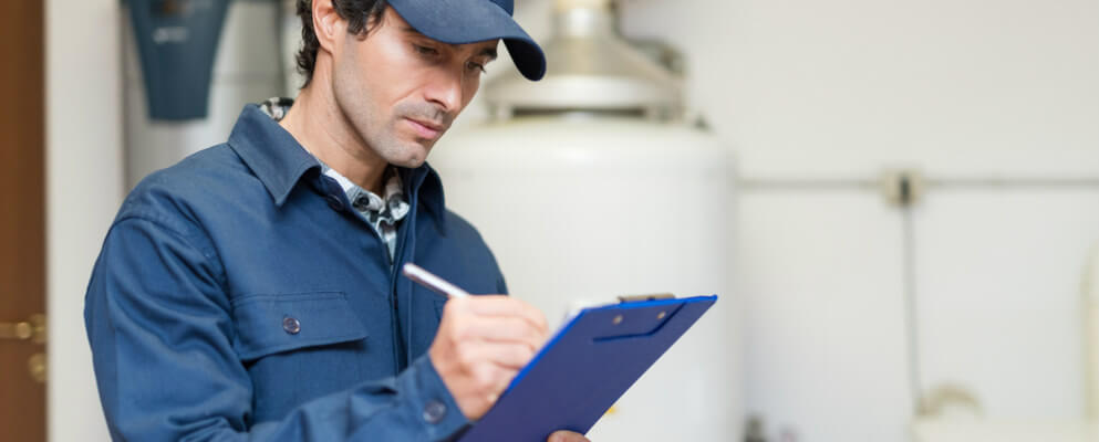man writing on industrial chiller maintenance checklist